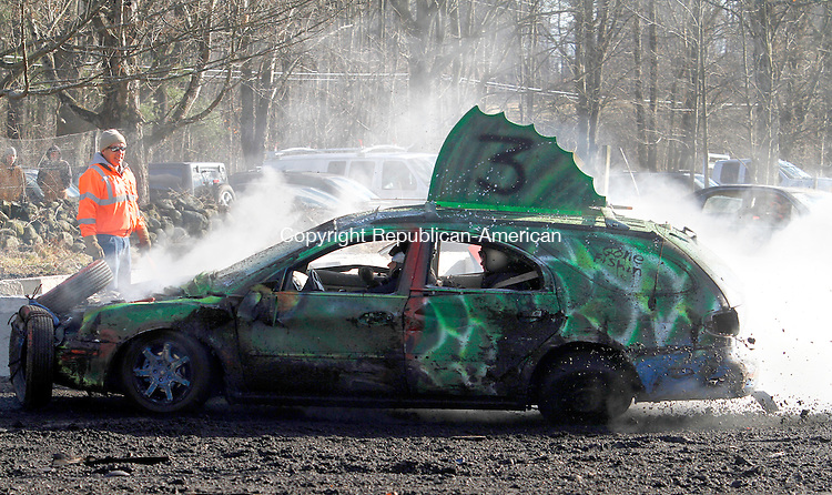 LITCHFIELD, CT.- 29 NOVEMBER 2013 - 112913JW07 - The Gone Fishin Ford wagon begins to smoke as it passes referee Dennis Meeker while racing around the oval track at the charity demolition derby at Meadow Ridge Farm Friday afternoon.<br /> Jonathan Wilcox Republican-American