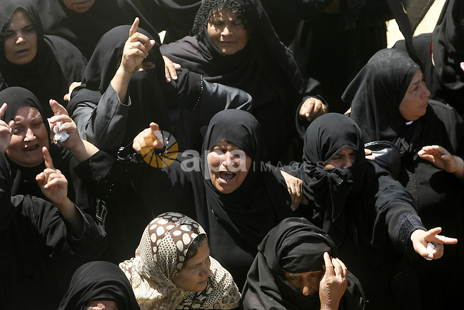 Relatives of Palestinian gunman Ahmed Nassir mourn during his funeral in Khan Younis in the southern Gaza Strip June 2, 2012. A Palestinian gunman, Ahmed Nassir, broke into Israel on Friday and killed a soldier before being shot dead himself in a rare cross-border attack that Israel blamed on the Islamist group Hamas. Photo by Eyad Al Baba
