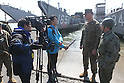 OSHIMA, Japan - Lt. Col. William Arick, commanding officer, Combat Logistics Battalion 31, 31st Marine Expeditionary Unit (left) and Capt. Masanori Ide, Japanese Ground Self Defense Force liaison officer to the 31st MEU (right), speak to Reuters media in front of U.S. Navy landing craft docked here, March 27. The 31st MEU and Amphibous Squadron 11 picked up Japanese utility repair vehicles from the port in Kessenuma and delivered food, water, comfort items and the vehicles to residents on this isolated island. The island of Oshima has been cut off from the mainland since the earthquake and tsunami March 11. The operation demonstrated the expeditionary capabilities in ship-to-shore amphibious operations. Marines and Sailors of the 31st MEU are conducting humanitarian aid and disaster relief missions in northeast Japan assisting the Japanese Self Defense Forces in their ongoing operations. (Photo by USMC/AFLO) [0006]