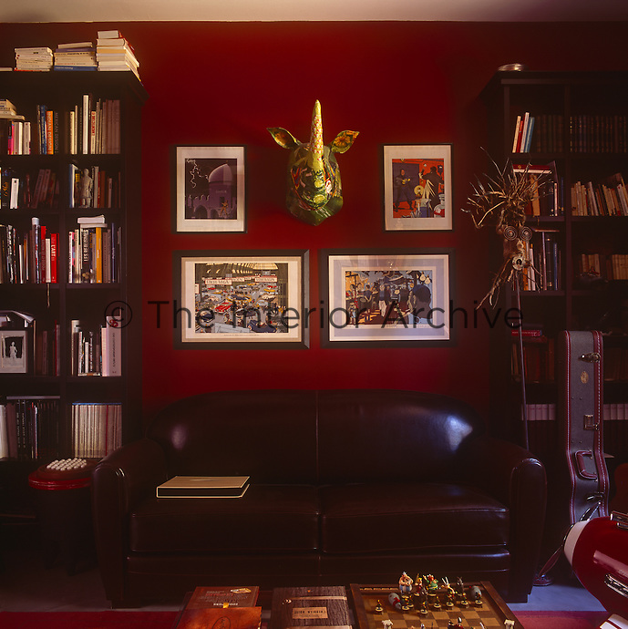 A red study with free-standing bookcases either side of a brown leather sofa. An arrangement of illustrative paintings are displayed on the wall.