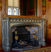 One of several gothic fireplaces in the library, each of which has slightly differently designed firedogs and hearth tiles
