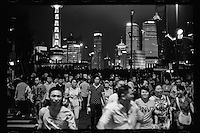 Visitors cross a main street at the Bund against a backdrop of the Pudong financial district in Shanghai, China, August, 2012. (Leica M6, 50mm f2, Kodak TRI-X 400)