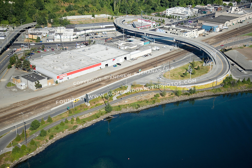 A sunny, summer afternoon aerial photo of the West Galer Street flyover in Seattle, Washington showing a necessary transportation overpass across busy Elliott Avenue and the BNSF railroad tracks that serve the Port of Seattle.  As Seattle has grown, development of prime waterfront space has put pressure on the working waterfront sections of the city.