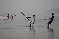 Beach fishermen pulling Gill net through surf, Goa, Arabian sea, India