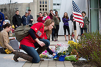 Biology grad student Eleanor Cameron places flowers at the memorial as people gather at a small memorial for slain MIT police officer Sean Collier between the STATA Center and Koch Institute on MIT's campus in Cambridge, Mass., on April 20, 2013.  Collier was shot and killed by the Tsarnaev brothers, suspects in the Boston Marathon bombings earlier that week.