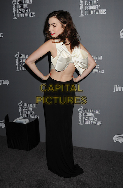 Lily Collins.15th Annual Costume Designers Guild Awards held at the Beverly Hilton Hotel, Beverly Hills, California, USA..February 19th, 2013.full length black sleeveless dress white bow ribbon back behind rear looking hands on hips over shoulder silk satin backless profile .CAP/ROT/TM.© TM/Roth/Capital Pictures