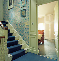 The first floor landing is decorated with vintage wallpaper