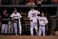 Aberdeen IronBirds Adley Rutschman (35) is greeted by manager Kevin Bradshaw (left) and Clay Fisher (19) after hitting a home run during a NY-Penn League game against the Vermont Lake Monsters on August 19, 2019 at Leidos Field at Ripken Stadium in Aberdeen, Maryland.  Aberdeen defeated Vermont 6-2.  (Mike Janes/Four Seam Images)