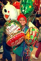 Boy age 6 holding balloons at soup kitchen Christmas dinner.  Minneapolis  Minnesota USA
