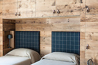 Twin beds with upholstered headboards are enclosed by a feature wall of built-in rough wood cupboards