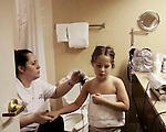 Madison, 5, at the hotel bathroom getting spray tanned before the Tu Tu Glitz on Tour beauty pageant. Atlanta, Georgia.