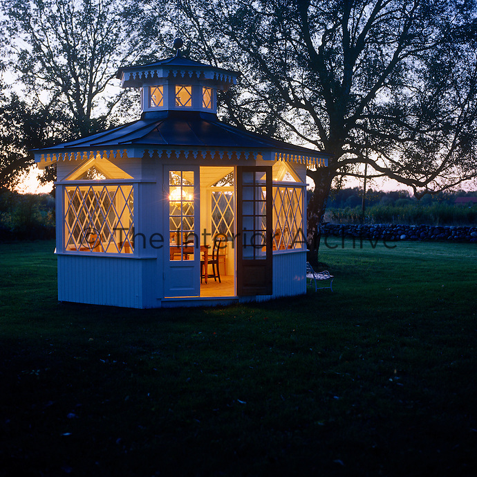 The gazebo is used as a summer dining room and is lit by a pendant light suspended from the ornate central cupola