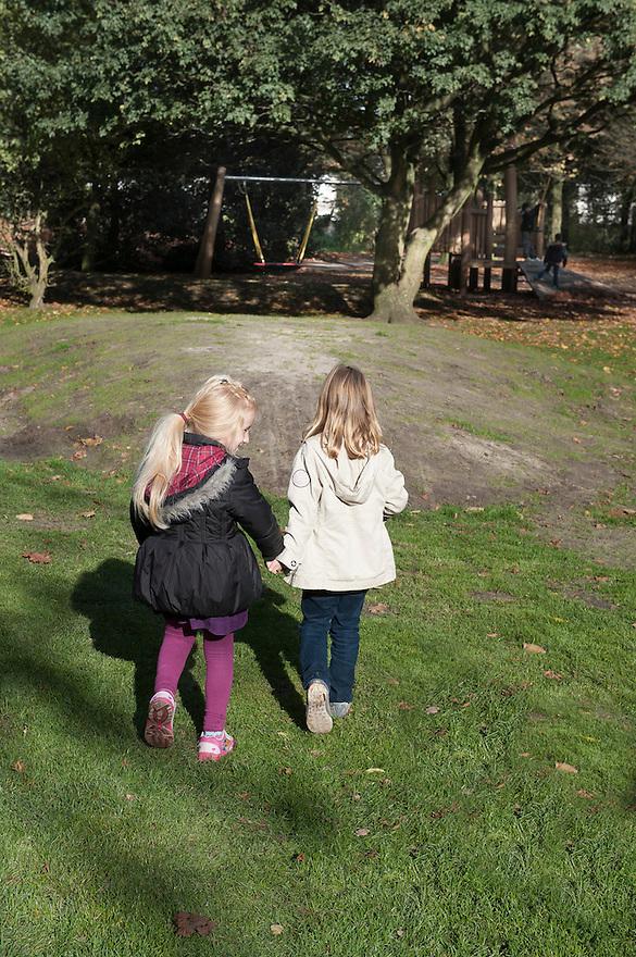 Nederland, Tilburg, 31 okt 2012.Twee meisjes, ongeveer 5 jaar oud, lopen hand in hand over een grasveld met speeltoestellen.Foto (c) Michiel Wijnbergh