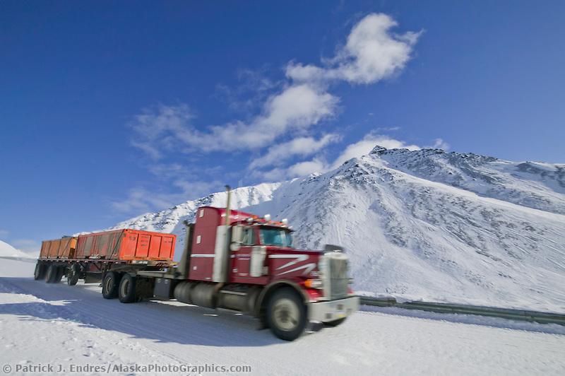 Semi tractor trailer hauls a load through Atigun pass on the James Dalton highway in winter.