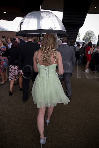13.04.2012 Aintree, England. The Grand National Festival Ladies Day. A woman clutching an umbrella as she makes her way towards one of the grandstands between the races.