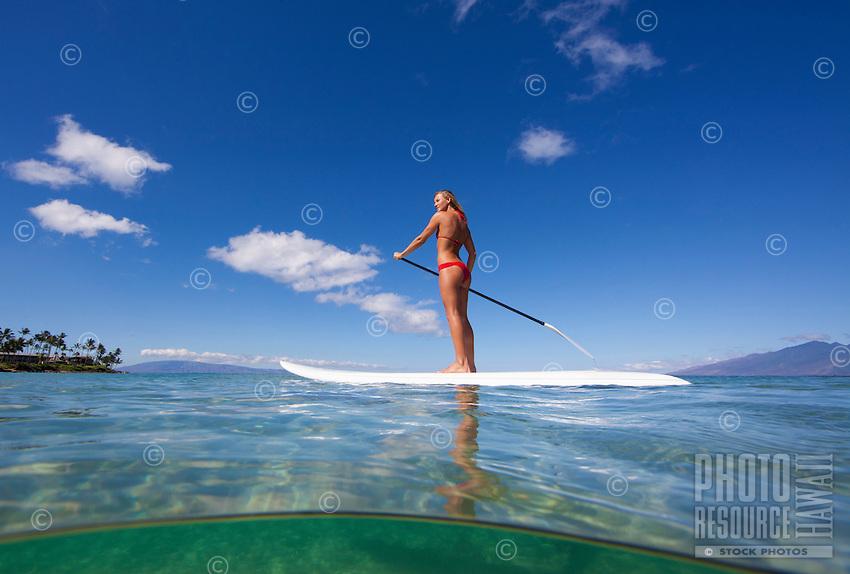 A healthy Maui girl standup paddles at Napili Bay, Maui.