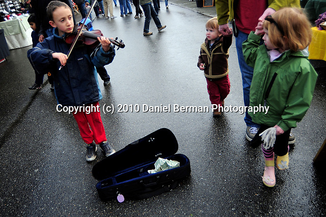 "Riley Deweese, 6, plays violin for passing patrons during opening day at the Bellingham Farmer's Market. Deweese has been playing for two years and says he plans to save any money he earns. ""I just want to play beautiful music,"" he said. Photo by Daniel Berman.."