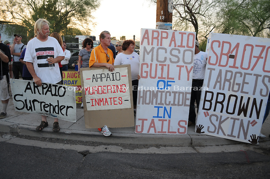 "Phoenix, Arizona. June 23, 2012 - Members of the Unitarian Universalist church and community advocates gathered outside the Tent City Jail in Arizona to demand  Sheriff Joe Arpaio to shut down what they call a ""concentration camp"" and inhumane outdoor jail facility. Tent City houses inmates in canvas tents and during the summer the temperature raises significantly under the tents. In this image, activists Rob McElwain (left) and Jorge Mendez (orange shirt),  long-time opponents of Sheriff Joe Arpaio, hold sign across the street where Arpaio was talking to reporters. Photo by Eduardo Barraza © 2012"