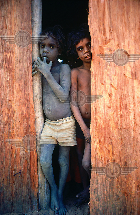 © Penny Tweedie / Panos Pictures..Aborigines, Arnhemland, AUSTRALIA...Two kids at Kalobidahdah outstation. Bark huts are a traditional form of shelter.