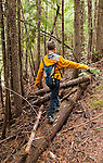 A seven year old boy balances on a fallen log along a trail near Priest Lake in Bonner County, Idaho