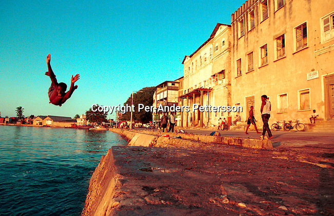 dicotanz00086 .Tanzania. Unidentified children jumping in the sea as the sun sets on July 22, 1997, in the old stone town in Zanzibar Town, Zanzibar, Tanzania. Zanzibar has a history both with slave trade and was ruled by Omani Arabs during the early 19th century. The Island is predominately Muslim and has become a popular tourist destination in recent years. The Island is a two hour boat ride from Dar es Salaam, Tanzania on the east African coast. The island is part of Tanzania. .©Per-Anders Pettersson/iAfrika Photos