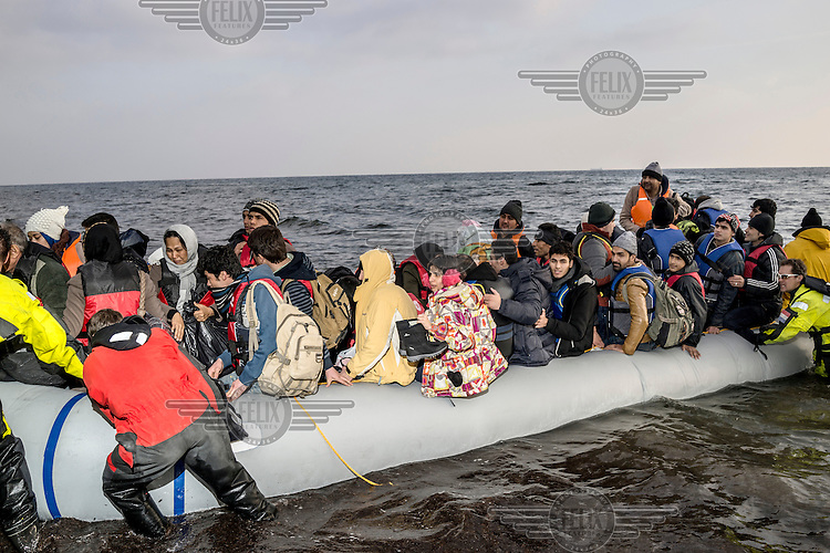 A boat crowded with refugees approaches the shoreline after crossing the Aegean Sea.