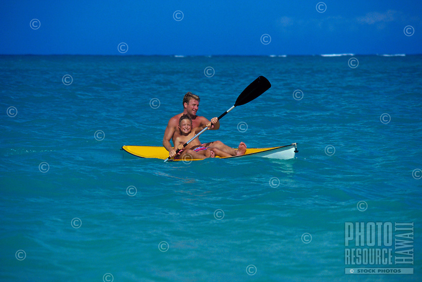 Father and son kayaking in bright blue water.