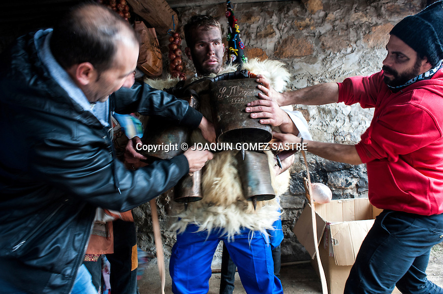 a character who plays a zarramaco is helped to get the campanos before the parade of carnival Vijanera.