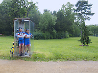 France. Paris. Bois de Boulognes. A group of four racing cyclists, all from asian ethnicity, stand inside a public phone booth. They protect themselves from the pouring rain. 06.06.10 © 2010  Didier Ruef