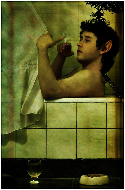 A young man sitting in the bath smoking a cigarette