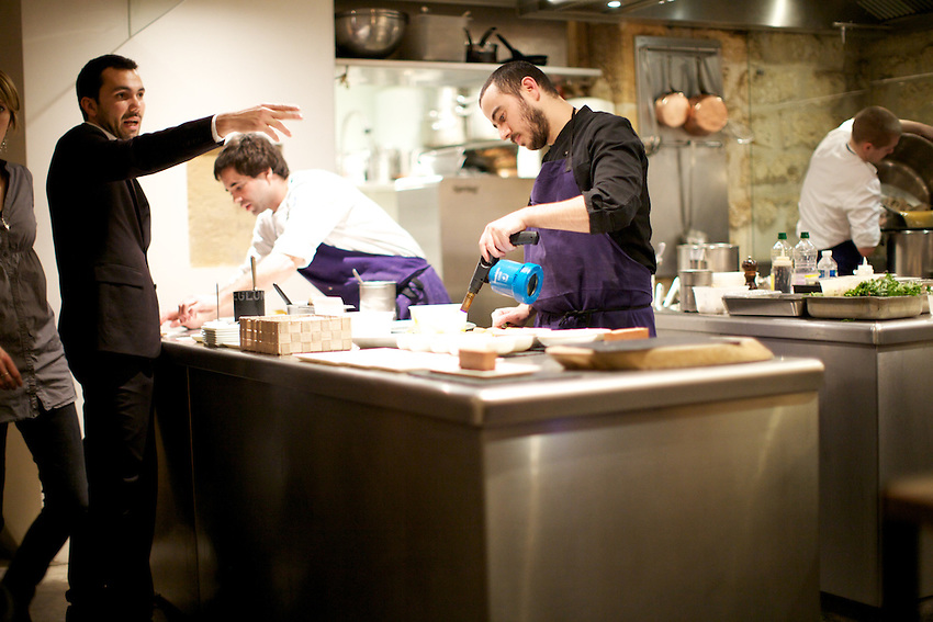PARIS, FRANCE - NOVEMBER 26, 2013: In the kitchen at Spring, an expeditor directs the staff, while chef Daniel Rose (center) finishes a dish with a blowtorch. CREDIT: Clay Williams.<br /> <br /> &copy; Clay Williams / http://claywilliamsphoto.com
