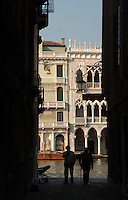 Two men silhouetted against Venetian ornate buildings on the Grand Canal. Venice, Italy, May 2007.