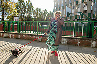 "Linda Oldham a five-year resident of the Cranbrook Estate with her dog. Behind the scenes of the ""Sucka Punch""  directed by Iggy LDN for the Uncertain Kingdom Project. Filmed on location at the Cranbrook Estate, Bethnal Green , East London"