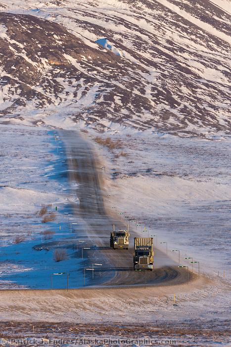 Semi tractor trailer trucks haul supplies along the James Dalton Highway in Alaska's Arctic.