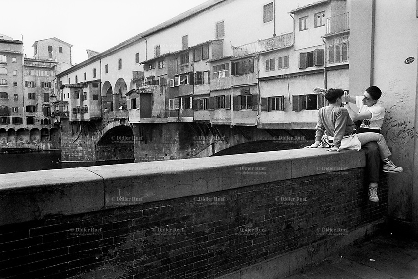 "Italy. Tuscany Region. Florence. A lovely teenage couple hugs and sits on a wall near the Ponte Vecchio. The man is making an obscene gesture with his right arm which meaning is ""vaffanculo"" (Fuck off! Get lost!). The Ponte Vecchio (""Old Bridge"") is a Medieval stone closed-spandrel segmental arch bridge over the Arno River, noted for still having shops built along it, as was once common. Butchers initially occupied the shops; the present tenants are jewelers, art dealers and souvenir sellers. Florence is the capital city of the Italian region of Tuscany and of the province of Florence. © 1993 Didier Ruef"