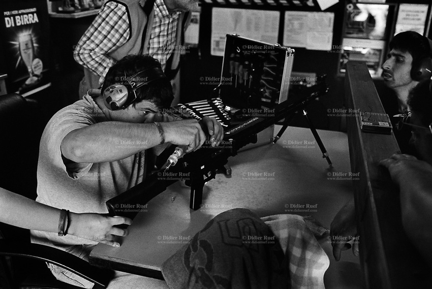 """Switzerland. Canton Ticino. Cureglia. Società Tiratori del Gaggio. Paolo Grassi is fixing the weapon belonging to a woman before her shooting practice. The SG 550 is an assault rifle manufactured by Swiss Arms AG (formerly Schweizerische Industrie Gesellschaft) of Neuhausen, Switzerland. """"SG"""" is an abbreviation for Sturmgewehr, or """"assault rifle"""". The rifle is based on the earlier 5.56mm SG 540 and is also known as the Fass 90 or Stgw 90. An assault rifle is a selective-fire rifle that uses an intermediate cartridge and a detachable magazine. 23.09.2017 © 2017 Didier Ruef"""