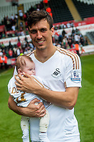 Jack Cork of Swansea City on the pitch with team players and staff during a lap of honour after the Barclays Premier League match between Swansea City and Manchester City played at the Liberty Stadium, Swansea on the 15th of May  2016