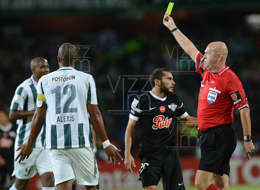 MEDELLÍN -COLOMBIA-21-04-2015. Heber Lopes (BRA), arbitro, muestra la tarjeta amarilla a Alexis Henriquez durante el encuentro entre Atlético Nacional de Colombia y Libertad de Paraguay por la fecha 6, fase 2, grupo 7, de la Copa Bridgestone Libertadores 2015 jugado en el estadio Atanasio Girardot de Medellín, Colombia./ Heber Lopes (BRA), referee, shows the yellow card to Alexis Henriquez during the match between Atletico Nacional of Colombia and Libertad of Paraguay for the 6th date, phase 2, group 7, of the Copa Libertadores championship 2015 played at Atanasio Girardot stadium in Medellin, Colombia. Photo: VizzorImage/ Leon Monsalve / Cont