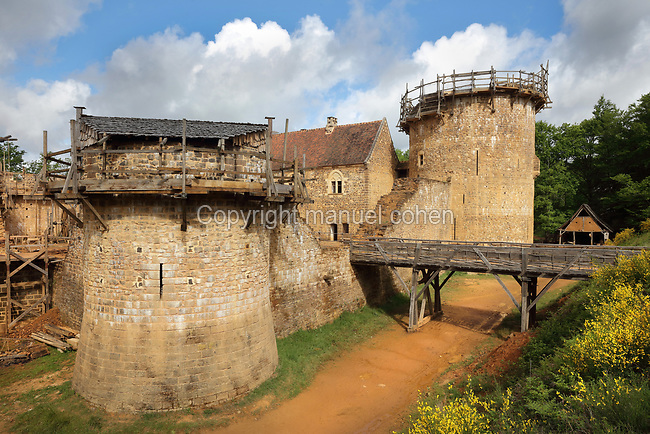 North Range or Logis Seigneurial in the centre, completed 2010, with the Great Tower or Tour Maitresse on the right, and Corner Tower on the left, still under construction, and footbridge over the moat trench, at the Chateau de Guedelon, a castle built since 1997 using only medieval materials and processes, photographed in 2017, in Treigny, Yonne, Burgundy, France. The Guedelon project was begun in 1997 by Michel Guyot, owner of the nearby Chateau de Saint-Fargeau, with architect Jacques Moulin. It is an educational and scientific project with the aim of understanding medieval building techniques and the chateau should be completed in the 2020s. Picture by Manuel Cohen