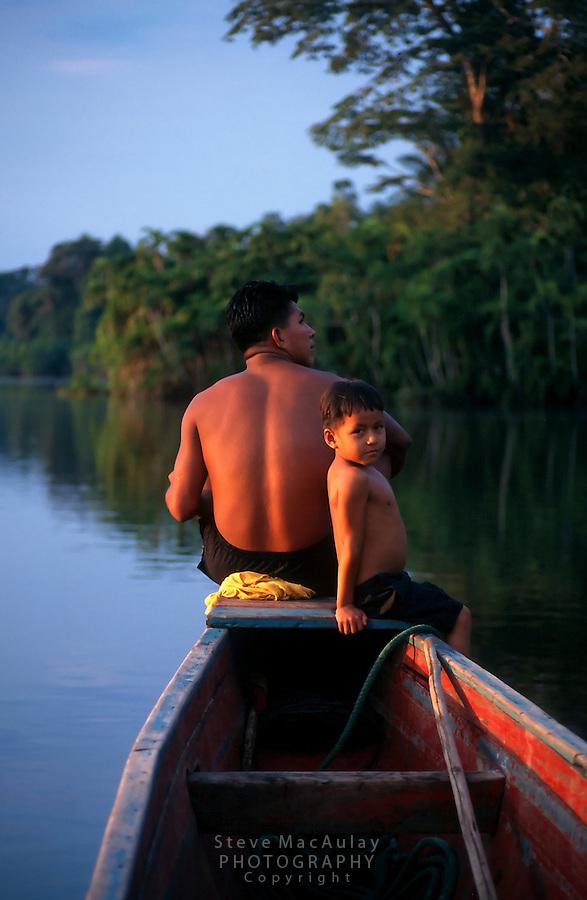 Indigenous boys on bow of river canoe, Lago Panacocha, Ecuado