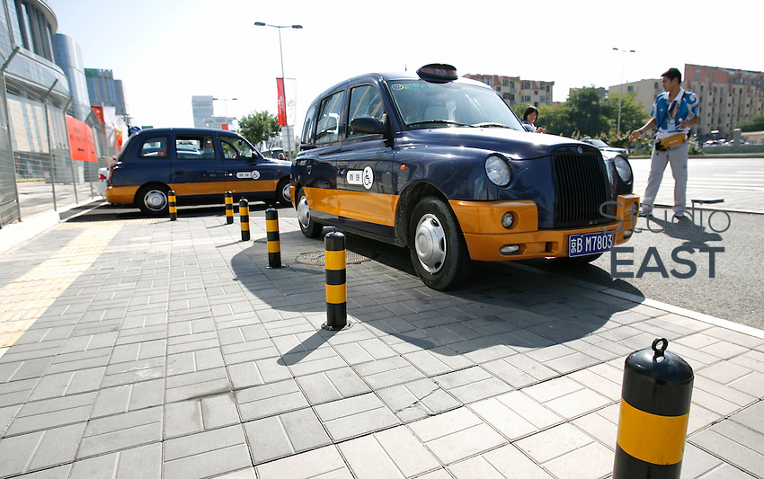 Two TX4 London Taxi cabs with wheelchair access are in service in Beijing, China during the 2008 Paralympics Games, on September 11, 2008. About 30 new wheelchair accessible TX4 London taxis, painted with the traditional colors of Beijing taxis, have been placed into service during the  Paralympic Games and will remain in the city afterwards. London Taxi International, the producer of London Taxi's famed black cabs, turned to China to drive overseas expansion. More than 8,000 London Taxis will be produced from the Chinese factory, more than double the annual output of the firm's historical factory plant in Conventry, England. Most of these cars will go to places like Singapore, Dubai, Moscow, that covet the image associated with the London Taxis' tradition of good service and durability. London Taxi International will continue to build 90 percent of the Taxi cabs used in Britain at Coventry. Photo by Lucas Schifres/Pictobank
