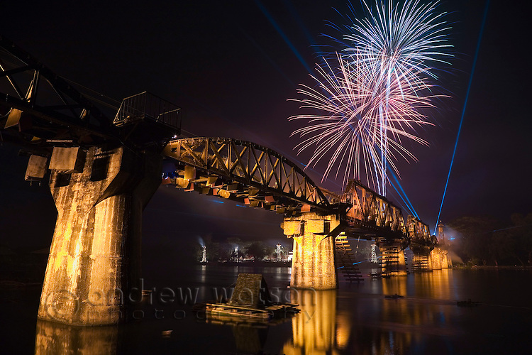 Fireworks explode over the the Death Railway Bridge (Bridge over the River Kwai) during the River Kwai Bridge Week festival.  Kanchanaburi, Kanchanaburi province, THAILAND.