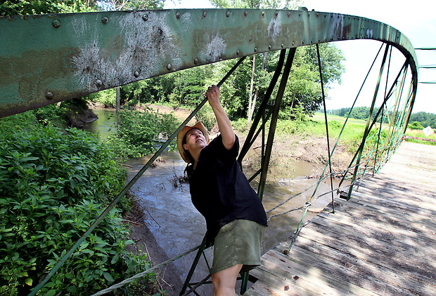 Julie Bowers, executive director of the North Skunk River Greenbelt Association, checks the condition of one of the arches on the McDowell Bridge spanning the North Skunk River in southwest Poweshiek County on June 22.  The arches began to lean last year after the bridge was damaged by an ice jam. The bridge, a bowstring truss, was built in 1883 by the King Iron Bridge Company of Cleveland, Ohio, and is considered one of the rarest and most historically significant types of bridges in the country.