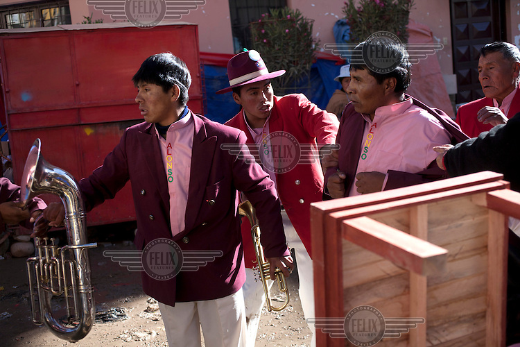 A band prepare to perform at the Carnaval de Oruro. During the fiesta many people sacrifice llamas and give offerings such as coca leaves and cigarettes to show their dedication to the Devil, a Virgin, Pachamama or Mother Earth. The Devil (or Uncle) is a mythical character that protects the miners of Oruro who work in dangerous conditions hundreds of metres below the ground. During the carnival, people dress in outrageous costumes and dance for days before arriving at the Church of Socavon, where they pay their respects to a virgin. Ironically, many of the dancers wear devil costumes.