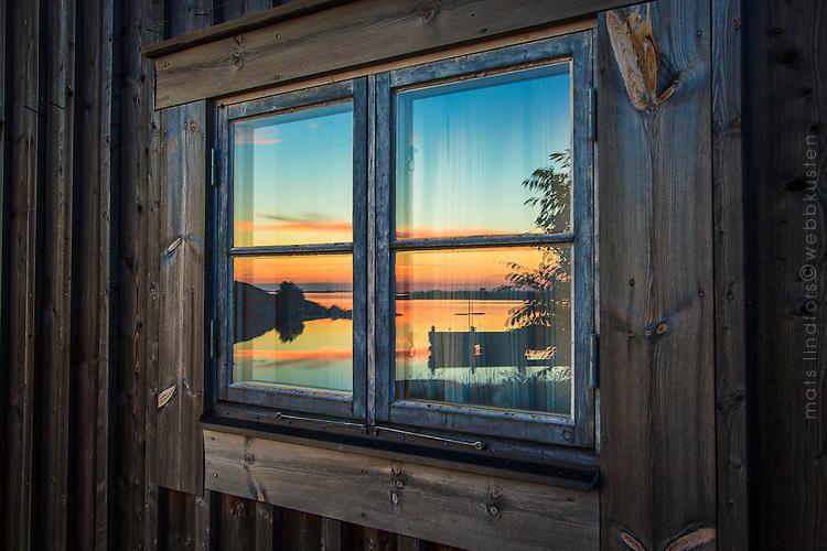 Fiskebod med solspegling i ett fönster på Ut-Fredel i Roslagen, Stockholms skärgård. / Fiskebod with solspegling in a window on Ut- Fredel i Stockholms archipelago Sweden.