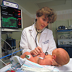 Doctor examining baby in nursery