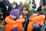 A girl hugs two younger sisters on a beach near Molyvos, on the Greek island of Lesbos, on October 31, 2015.  The girls had just arrived in a boat full of refugees that departed from from Turkey. They and their parents were received by local and international volunteers, then proceeded on their way toward western Europe. The boat was provided by Turkish traffickers to whom the refugees paid huge sums to arrive in Greece.