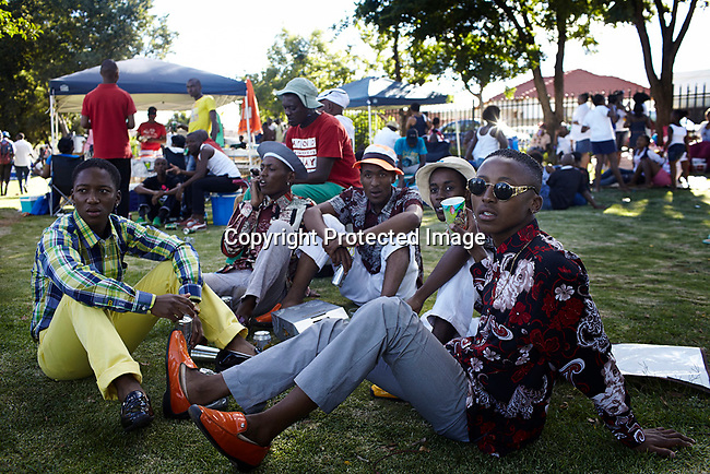 SOWETO, SOUTH AFRICA DECEMBER 16: A group of Izikhothane youths who call themselves the ìItaliansî relax in a park on December 16, 2012 in Soweto, South Africa. Many of Izikhothane kids gather in parks and to show off their dance moves, play loud music and impress on girls. The Izikhothane bling kids are the new fears of residents and parents in the townships of Johannesburg. They buy (and sometimes burn and destroy) fancy brand clothes and shoes. They also like to drink and display expensive bottles of alcohol. Many of these kids are desperate to get the latest clothes and the pressure is hard on their parents. (Photo by: Per-Anders Pettersson)