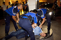 Switzerland. Geneva. Paquis neighborhood. Three police officers arrest a drunk man in front of the main entrance of the Grand Hotel Kempinsky Geneva, a Luxury 5 star hotel. The handcuffed inmate is a wealthy russian man has caused a fight and is under the influence of alcohol. The policewoman (C) is wearing a ballistic vest, bulletproof vest or bullet-resistant vest which is an item of personal armor that helps absorb the impact from knives, firearm-fired projectiles and shrapnel from explosions, and is worn on the torso. Soft vests are made from many layers of woven or laminated fibers and can be capable of protecting the wearer from small-caliber handgun and shotgun projectiles, and small fragments from explosives such as hand grenades. 11.05.12 © 2012 Didier Ruef.... *** Local Caption *** ..