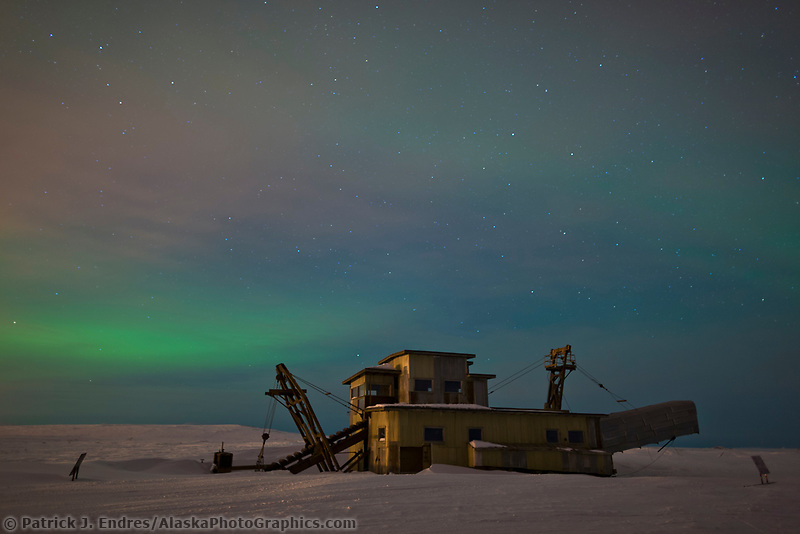 Aurora borealis over a historic dredge outside the town of Nome, Alaska on the Seward Peninsula.